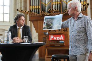 Gespreksleider Aart van Cooten houdt een foto van Koenders' geboortestad voor.